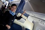 ANA flight attendant demonstrates the new overhead baggage compartment.