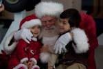 Two children get a hug from Santa after their visit. (Photo by Jeremy Dwyer-Lindgren)
