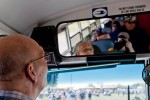 A volunteer bus driver checks up on departing passengers while making a stop on the AirVenture bus route.