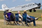 Four long-time Oshkosh attendees wait for the visiting Junkers JU-52 (HB-HOT) to clear the runway and begins its demo.