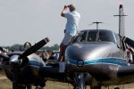 An owner stands on the wing of his twin-prop to watch the show.