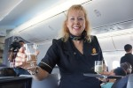 A flight attendant offers champagne in Business First. United 787 inaugural in-flight Business First aboard United's first 787 Dreamliner service. (Photo by Chris Sloan-Airchive.com)