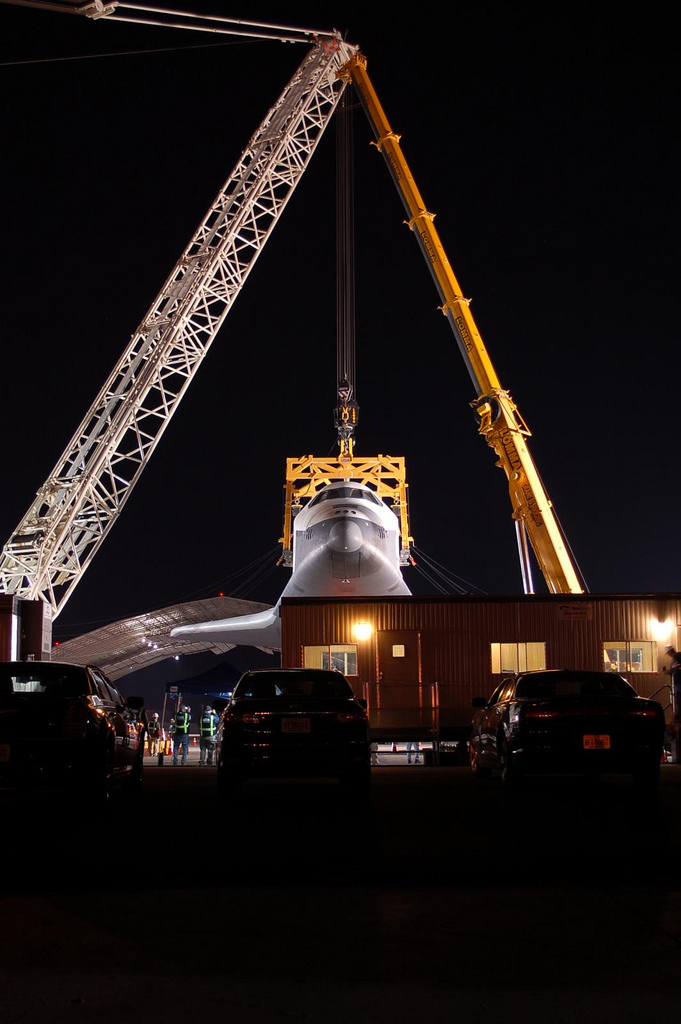 Space Shuttle Enterprise held by two cranes. (Photo by Guy Dickinson, CC BY-SA)