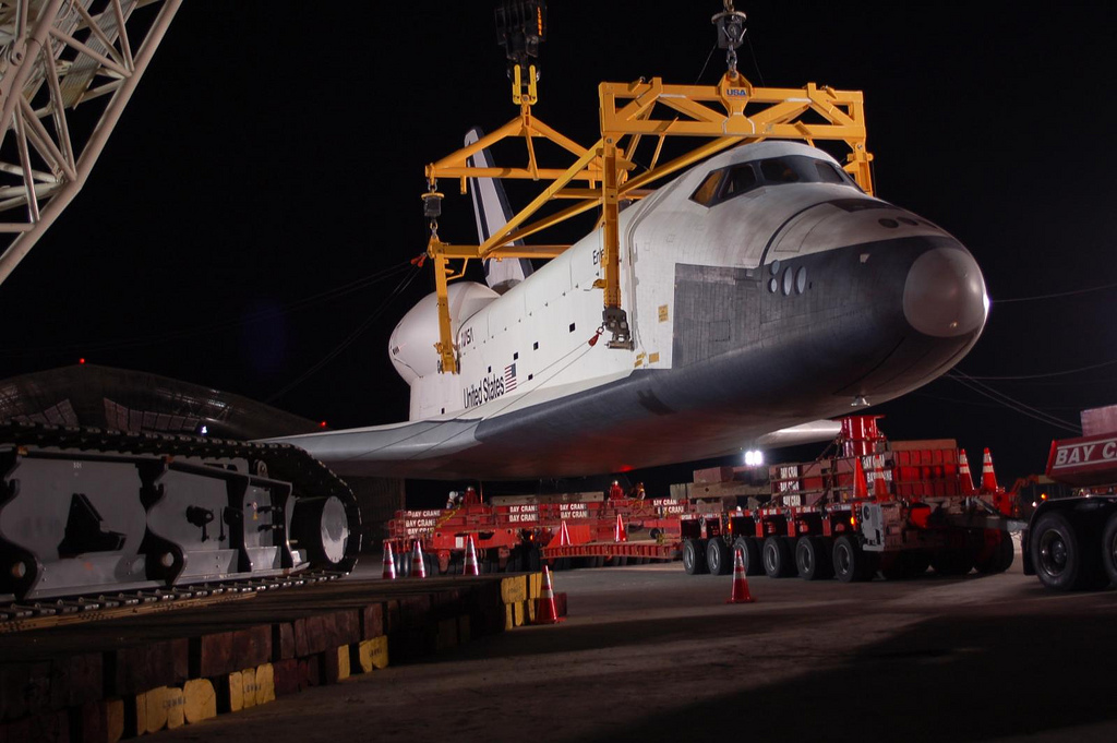 Space Shuttle Enterprise is lowered onto a custom trailer. (Photo by Guy Dickinson, CC BY-SA)