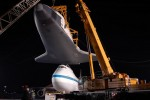 With Enterprise held by two cranes, the Shuttle Carrier Aircraft is pushed back. (Photo by Guy Dickinson, CC BY-SA)