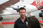 <em>Real Steel</em> star Hugh Jackman addresses media with his co-star World Robot Boxing contender Atom in the background. (Photo by Stephen Shrank)