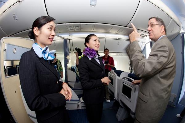 ANA flight attendants Maki Sakatani, left, and Kyoko Kouokawa, right, talk with 787 program VP Scott Francher on board.