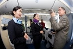 ANA flight attendants Maki Sakatani, left, and Kyoko Kouokawa, right, talk with 787 program VP Scott Francher on board.