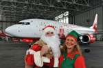 Santa Claus and one of his elves pose in front of the Air Berlin Santa Claus Tour 2012 Boeing 737 (D-ABMJ). (Photo by Air Berlin)