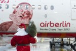 Santa Claus admires his portrait on the side of Air Berlin's Santa Claus Tour 2012 Boeing 737 (D-ABMJ). (Photo by Air Berlin)