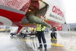 A baggage handler loads a Christmas tree onto Air Berlin's Santa Claus Tour 2012 Boeing 737 (D-ABMJ). (Photo by Air Berlin)