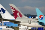 Tail fins of a Korean Air Boeing 737-900ER, a Qatar Airways Boeing 787-8 Dreamliner, and a Malaysia Airlines Airbus A380. (Photo by Farnborough International)