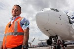 "Ramp duty manager Albert Cordeschi (""Ramp Ringleader"") poses on the runway underneath an airplane. (Photo by Travel Channel)"