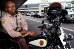 """Miami-Dade County motorcycle officer Stretch Rutledge (""""MIA's Gentle Giant"""") poses on his motorcycle by the departures drop-off at MIA. (Photo by Travel Channel)"""