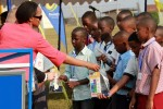 Boeing reps and the Minister of Infrastructure hand out gifts to a group of schoolchildren.
