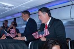 President Obama (Reggie Brown) and Governor Romney (Jim Gossett) handing out American flags at 35,000'.