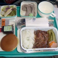 "One of Garuda Indonesia's inflight meals...which seems to be from a children's menu, consisting of bacon and peapods with a side of Big League Chew and an ""Elf-style"" bottle of maple syrup."