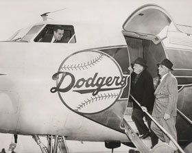 "Bump Holman stands in front of the DC-3 with Lee Pike, his first flight instructor and first co-pilot with the Dodgers in 1954. Holman got his commercial pilot's license at the age of 18. Photo by Barney Stein 	     	The Brooklyn Dodgers Convair 440 Metropolitan twin-engine plane was purchased on January 4, 1957. The Dodgers took delivery of the plane in mid-March. At the time of purchase, Dodger President Walter O'Malley announced to Associated Press, ""This is the first time a major league club has bought an airplane."" 	     	Dodger President Walter O'Malley and Dodger Director Bud Holman are on the steps of the 44-seat Dodger Convair 440 Metropolitan twin-engine plane. Holman's son Bump is visible in the cockpit window. O'Malley added to the order of Eastern Air Lines to purchase the plane directly through the Convair factory, with the assistance of his friend Capt. Eddie Rickenbacker, President of Eastern. Bud Holman served as a Director of the Dodgers and was Eastern's representative at the Vero Beach Airport. 	     	The Dodgers became the first major league baseball team to own their own airplane, as they purchased a Convair 440 Metropolitan twin-engine. From left to right, Capt. Eddie Rickenbacker, President of Eastern Air Lines, Dodger Director Bud Holman, Dodger President Walter O'Malley and Dodger Director James Mulvey show a model of the Convair 440. The Dodgers made the purchase of the airplane on January 4, 1957, piggybacking on Rickenbacker's order of airplanes for Eastern."