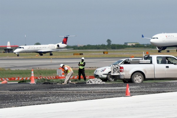 Construction personnel are seen completing work on the north side of the Bay Runway as two arriving aircraft taxi to the terminal
