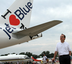 JetBlue CEO David Barger poses with the I Heart JetBlue Airbus A320 at Oshkosh 2011.