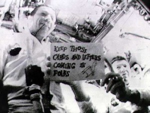 Commander Wally Schirra, Command Module Pilot Donn Eisele and Lunar Module Pilot Walter Cunningham holding up a sign during the first live broadcast from space aboard Apollo 7.