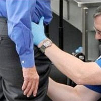 TSA agent pats down an airport passenger.