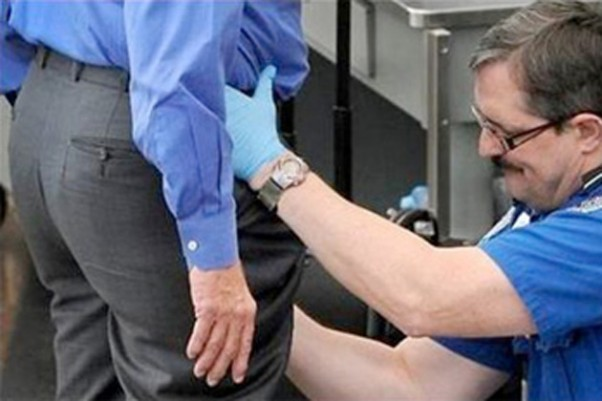 TSA agent pats down an airport passenger.