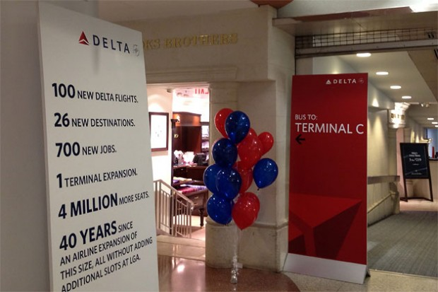 A sign adjacent to the SkyClub in the main Delta terminal directs passengers to the bus stop for Terminal C. Another sign touts the benefits of the airline&#039;s massive expansion. (Photo by Matt Molnar)