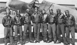 Eight Tuskegee Airmen pose in front of a P-40, circa May 1942 to Aug 1943.