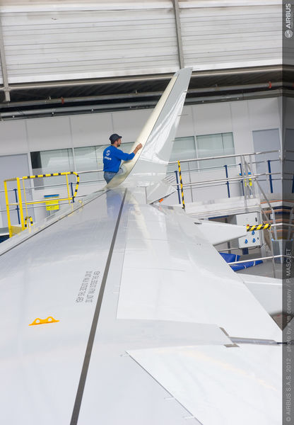 An Airbus employee attaches a Sharklet to the wingtip of an A320. (Photo by Airbus)
