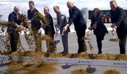 Delta executives, New York Mayor Mike Bloomberg and other local politicians take part in the ceremonial first dig for the 630-foot long bridge that will connect Terminals C and D.