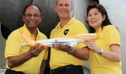 Scoot executives pose with a model Boeing 777 with a full-size version in the background. (Photo by Scoot)