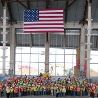 LAWA staff, construction workers from Walsh-Austin Joint Venture, and special guest, veteran Pete Howenstein pose in the great hall of the South Concourse with an American flag during a pre-Memorial Day tribute, May 24, 2012. (Photo by Stephen Shrank/NYCAviation)