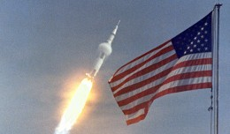 Apollo 11 flies towards earth orbit with the American flag in the foreground. (Photo by NASA)