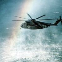 A rainbow is formed in the mist rising from the ocean as a Helicopter Mine Countermeasures Squadron 15 (HM-15) MH-53E Sea Dragon helicopter conducts mine countermeasures operations near Naval Air Station, Alameda, Calif. (Photo by John Gaffney/US Navy)