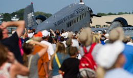 The crowd looks to the sky in unison at the F18 above them while the JU-52 rests.