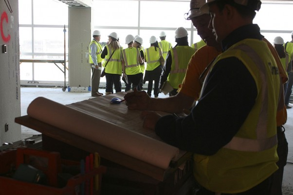 Construction workers examine blueprints inside the new Sky Club.