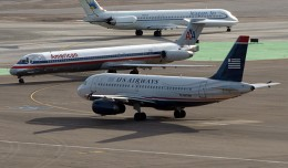 An American Airlines MD-80 and a US Airways A319 meetup while an Allegiant MD-80 rolls by in Vegas. (Photo by g Tarded via Flickr, CC-BY-ND)