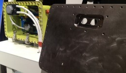 The new 787 battery enclosure adds another layer of protection and eliminates the potential for fire. At right is cover for the enclosure, which is made of 1/8-inch stainless steel. (Photo courtesy   Boeing)