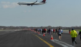 A Delta Boeing 737 on short final for runway 31R as JFK Runway Run participants run down runway 4R.