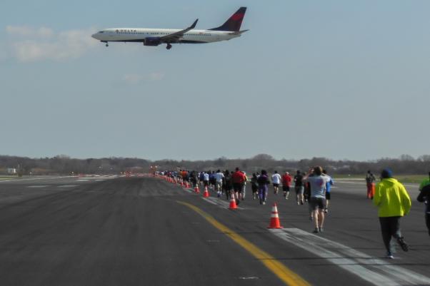 A Delta Boeing 737 on short final for runway 31R as JFK Runway Run participants run down runway 4R.