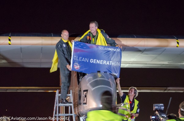 The Solar Impulse crew holds up a banner after completing their cross crountry journey