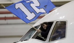 "The ""12th Man"" flag is waved out the cockpit window as the Seattle Seahawks arrive at Newark. (Photo: AP)"