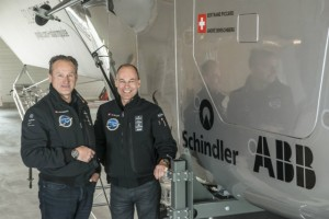 (From left to right) André Borschberg, Co-founder and CEO and Bertrand Piccard, Initiator and Chairman are standing beside the cockpit of Solar Impulse 2, the single seater solar airplane with which they will attempt in 2015 the first round-the-world solar flight. Image courtesy of Solar Impulse.
