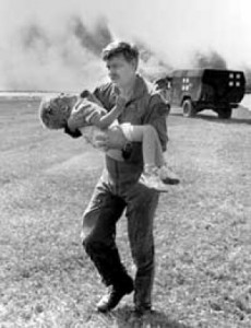 Lt. Colonel Dennis Nielsen carries Spencer Bailey, a young survivor,  to safety following the crash. (Wikipedia)
