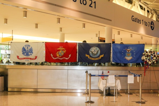 The flags of the Army, Marine Corps, Navy, and Air Force, displayed in JFK's Terminal 5. Below them is a fallen comrades table ceremony, honoring those killed and missing in action.