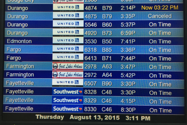 The departure board at DIA shows United and Southwest flights to Fayetteville. Photo by Paul Thompson.