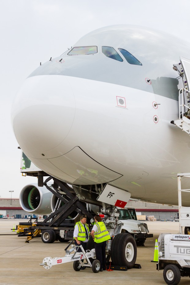 Personnel stand under the nose of the superjumbo while the aircraft is serviced.