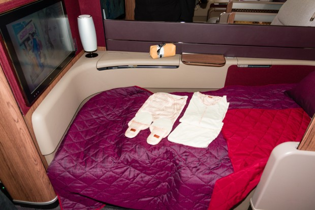 A first class seat that has been transformed into a bed.