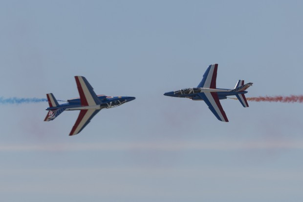 The two Patrouille de France solos cross while rolling at show center.